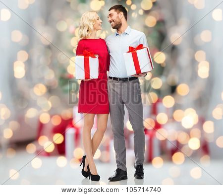 people, christmas, birthday, couple and holidays concept - happy young man and woman with gift boxes over christmas tree lights background