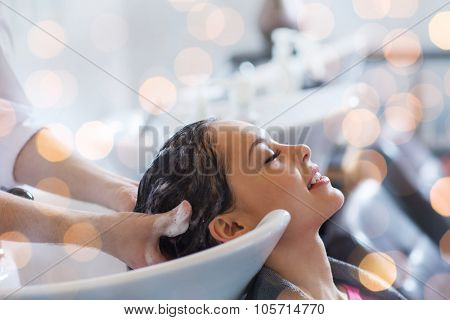 beauty, hair care and people concept - happy young woman with hairdresser washing head at hair salon over holidays lights