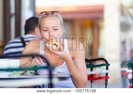 Woman eating pizza outdoor in cafeteria.