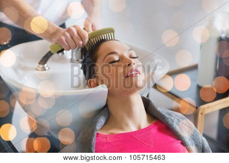 beauty, hair care and people concept - happy young woman with hairdresser combing wet hair after washing at salon over holidays lights