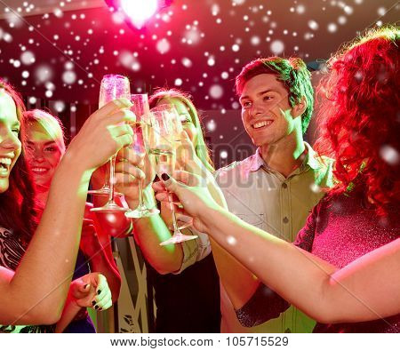 new year party, holidays, celebration, nightlife and people concept - smiling friends clinking glasses of non-alcoholic champagne in club and snow effect