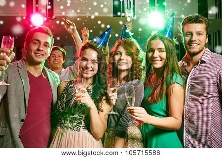 new year party, holidays, celebration, nightlife and people concept - smiling friends in party caps with glasses of non-alcoholic champagne in club and snow effect