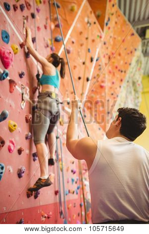 Instructor guiding woman on rock climbing wall at the gym