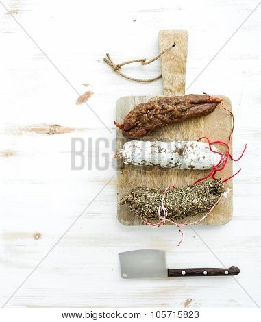 French alsacian smoked salamis on rustic wooden chopping board over white backdrop, top view