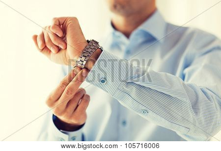 people, business, accessories and clothing concept - close up of man in shirt fastening wristwatch at home