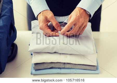 business, trip, luggage and people concept - close up of businessman packing clothes into travel bag