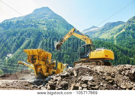 excavator loads the ground in the stone crusher machine during earthmoving works outdoors at mountains construction site