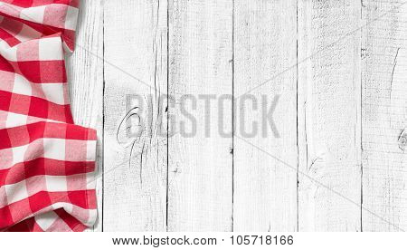 red picnic tablecloth on white wood table background