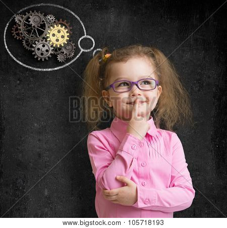 kid girl in glasses with bright idea standing near school blackboard