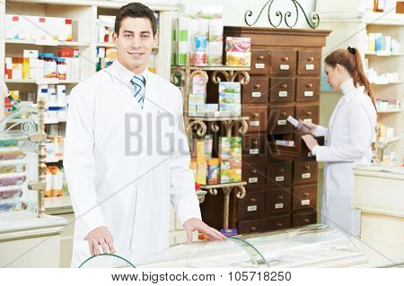 young pharmacist chemist man and woman  standing in pharmacy drugstore