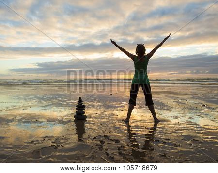 Silhouette of a woman with open arms at the beach close to a stones pile