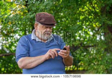 Portrait of bearded senior man using cellular phone outdoor