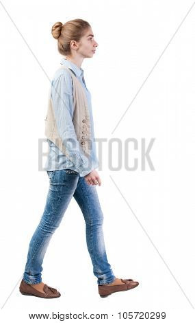 side view of walking  woman in vest. beautiful girl in motion.  backside view of person.  Rear view people collection. Isolated over white background. Girl with a bun of hair out sideways