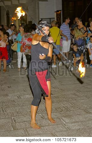 A young and stylish dancer with torches Fire performs in the square of Putignano Puglia. Italy