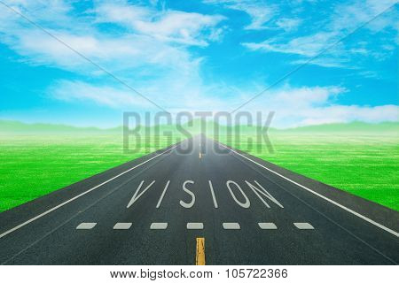 Road Through The Green Field With Sign Vision On Asphalt