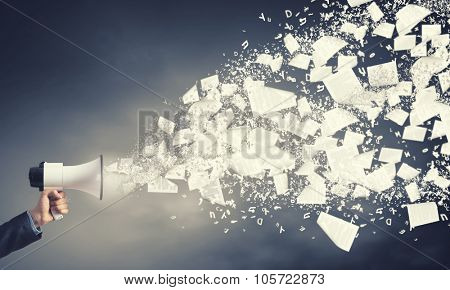 Businessman hand with loudspeaker and papers flying out