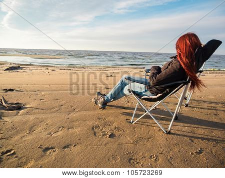 woman sitting on deckchair at sunset on beach