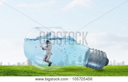 Young businessman in suit and diving mask swiming in lightbulb with water
