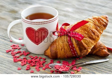 Cup Of Tea With Croissants Heart Shape Decoration On Wooden Background