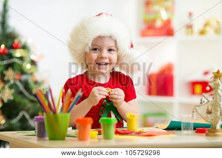 Kid girl making by hands x-mas decorations