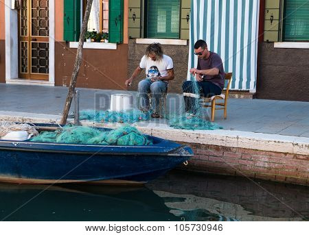 Fishermen Repair Their Nets After A Night Of Fishing.