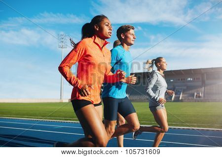 Runners Running On Race Track In Stadium