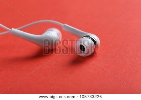 White Headphones On A Red Paper Background