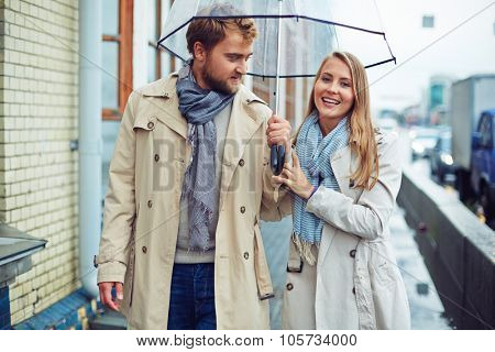Amorous man and woman walking under umbrella