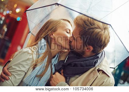 Amorous young couple kissing under umbrella