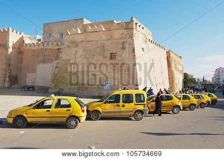 Taxis wait for passengers in from of the medina wall in Sfax, Tunisia.
