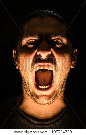 Horror Scene With Screaming Scary Human Face With A Harsh Light On A Black Background - Halloween