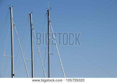 Sailing Boat Poles Against Blue Sky Background.