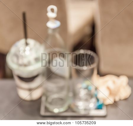 Blurred Photo Of Empty Coffee Cup And Water Bottle After Finished Coffee Break Time.