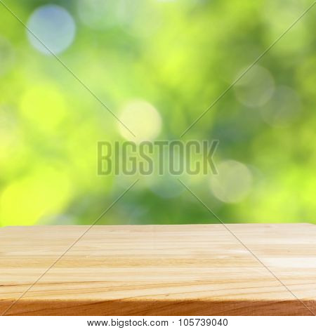 wood table and blurry green nature in background