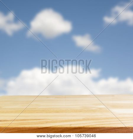 wood table and blurry blue sky in background