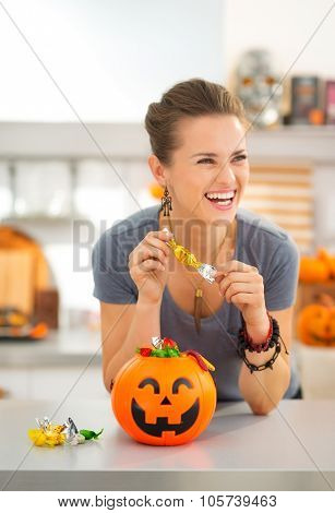 Woman Eating Trick Or Treat Candy In Halloween Decorated Kitchen