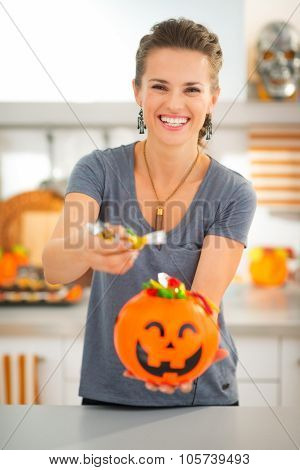 Woman Holding Halloween Bucket And Giving Trick Or Treat Candy
