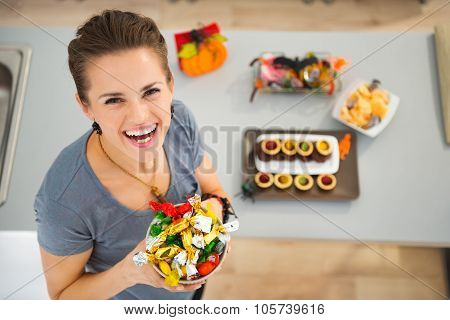 Woman Holding Dish With Halloween Trick Or Treat Candy