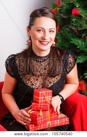 Happy woman holding red gift boxes