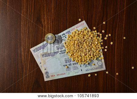 Indian grain and pulses market rates. Hundred Rupees currency notes and coins in the with Tur Dal pulses.