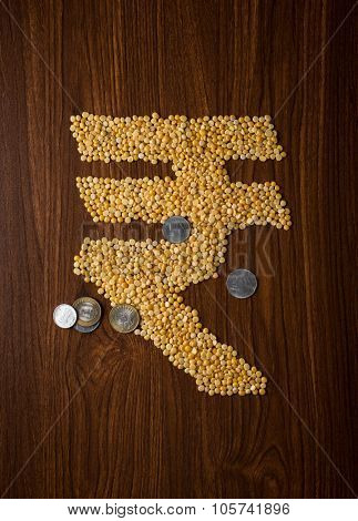 Tuvar Dal (Indian split lentils) in 'Rupee' symbol shape with few coins. Food price in India concept.