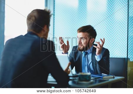 Handsome employee explaining his point of view to colleague at meeting