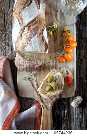 French Country Bread, Cherry Tomatoes, Olives And Wineglass