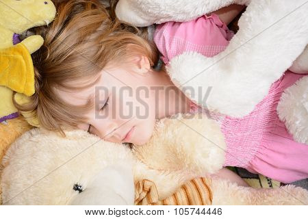 Little Girl Lies Among Stuffed Toys