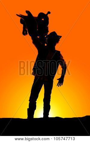 Silhouette Of A Cowboy Holding A Saddle Up High