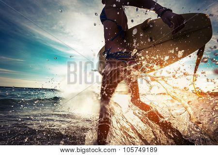 Lady with surfboard running into the sea with lots of splashes