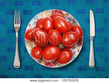 red tomatoes on white plate, knife and fork