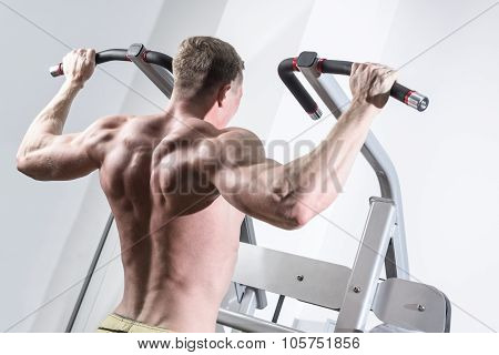 Bodybuilder training in the gym. Athlete doing Pull-Ups