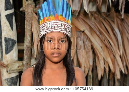 IQUITOS, PERU - OCTOBER 18, 2015: A young girl of the Bora Tribe in Peru. Portrait of a native girl in traditional costume standing in front of a typical hut.