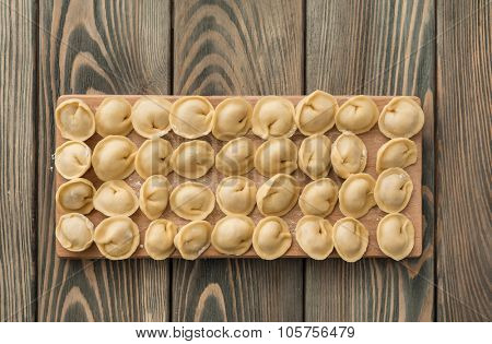 Uncooked dumplings with meat on the wooden desk.